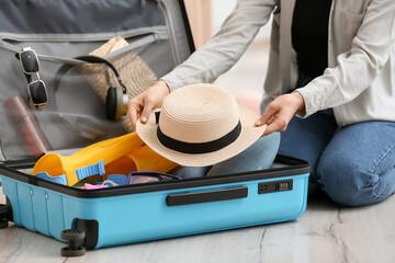 Fototapeta Woman packing suitcase at home obraz