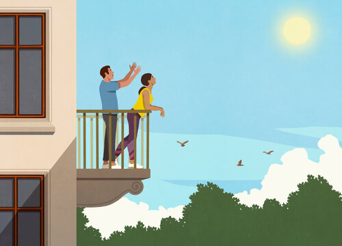 Happy couple enjoying sunshine on apartment balcony