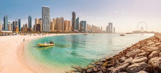 Fototapeta Wide panorama of the Persian Gulf with sandy beach and Bluewaters Island with the worlds famous largest Ferris wheel Dubai Eye and numerous skyscrapers with hotels and residences obraz