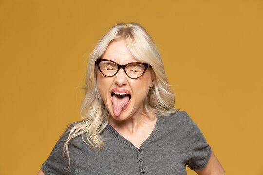 Studio portrait playful woman sticking tongue out