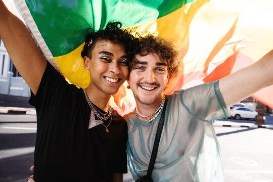 Smiling queer men celebrating gay pride outdoors
