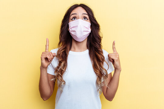 Young mixed race woman wearing a protection for virus isolated on yellow background pointing upside with opened mouth.