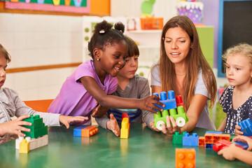Kinder spielen zusammen mit bunten Bausteinen