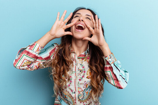 Young mexican woman isolated on blue background shouting excited to front.