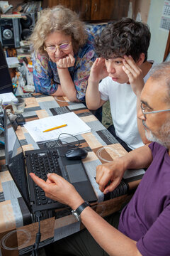 Grandson being Taught by his Grandparents is Amused in front of Laptop at Home