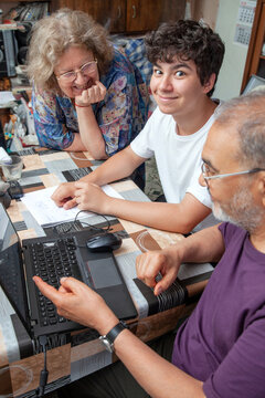 Happy Teenage Boy Smiling while being Taught by his Grandparents at Home