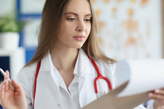 Young female doctor examines medical history of patient