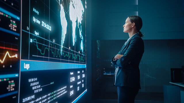 Young Female Computer Science Engineer Looking at Big Screen Display Showing Global Map with Data Points. Telecommunications Technology Company System Control and Monitoring Room with Servers.