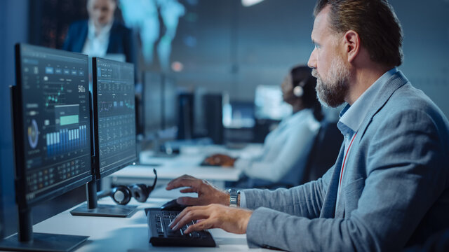 Portrait of Serious Professional Technical Controller Sitting at His Desk with Multiple Computer Displays Before Him. In the Background His Colleagues Working in System Control and Monitoring Center.