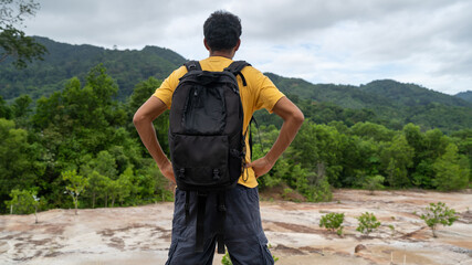 Young traveler man with backpack standing relax against landscape scenery mountain peak in phuket thailand