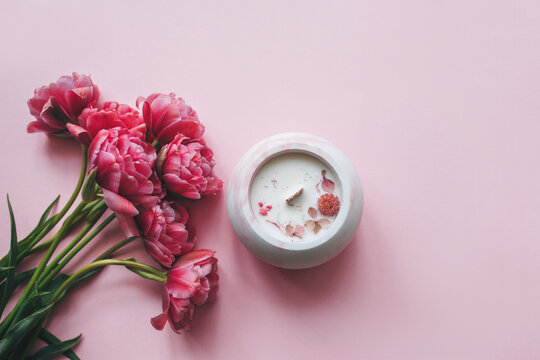 Ecological and vegan handmade candle with dry flowers in a glass made of concrete on a pink background with pink tulips. Soy or coconut candle with a wooden wick.