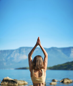 Back view woman practices yoga with hands up pose at nature with beutiful mountains view. Body and mental welness