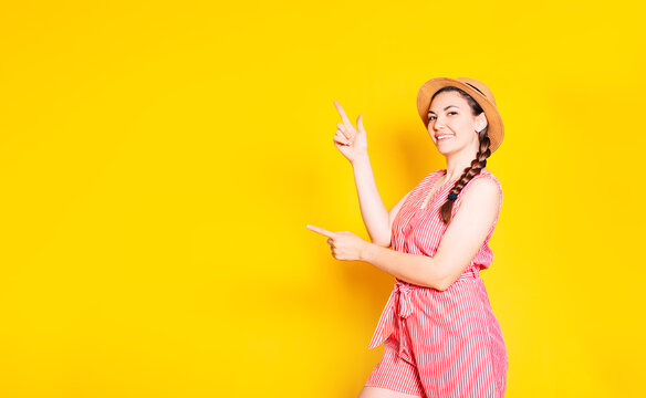 A photo of a happy young woman standing isolated against a yellow wall. We look at the camera showing where copy space points.