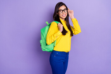 Photo of charming nice happy woman look empty space hold glasses backpack isolated on violet color background Wall mural
