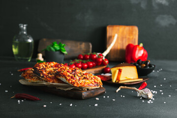Obraz Pizza. Mini italian pizzas with cheese, pepper and tomatos. Pizza on wooden plate. - fototapety do salonu