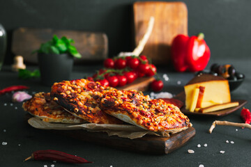 Fototapeta Pizza. Mini italian pizzas with cheese, pepper and tomatos. Pizza on wooden plate. obraz