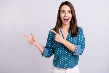 Photo of impressed brunette hair young lady point empty space wear blue shirt isolated on grey color background Wall mural