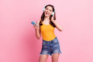 Photo of pretty cute young woman wear yellow singlet listening music holding modern gadget isolated pink color background Wall mural