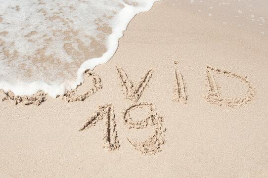 Sea wave sweeps inscription COVID 19 on a sandy beach