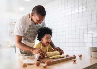 Fototapeta Happy Smiling African American Father and Adorable Son have fun Cooking and kneading dough in white kitchen. Playful Black Family baking cookies together obraz