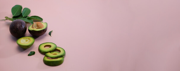 Fresh whole and sliced avocado isolated on pink background.