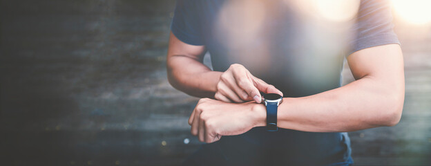 Fototapeta Athletic man using fitness tracker or smart watch between run training outdoors.  obraz