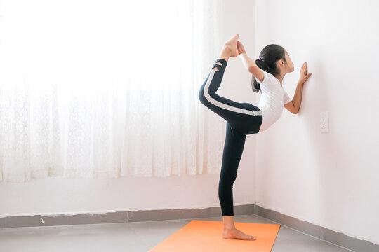 Niña mexicana practicando yoga sobre un tapete naranja a contraluz