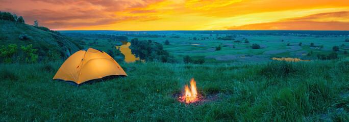 Orange tourist tent on hill above river under orange dramatic sky