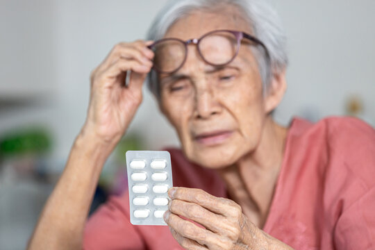 Asian old elderly trying to read medicine label that has small font,problem with very small letters of drug labels or tiny text on products information making her unable to see clearly what is written