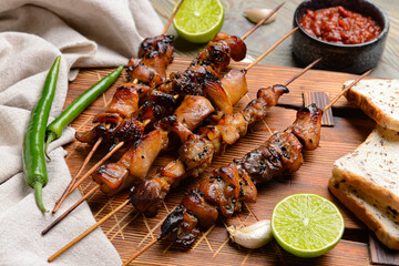 Board with tasty chicken kebab on wooden background