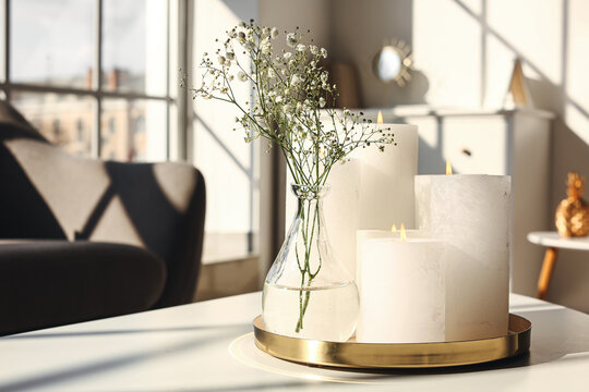 Tray with candles and flowers on table in living room