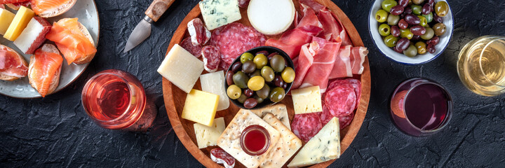 Fototapeta Italian antipasti or Spanish tapas panorama. Gourmet cold meat and cheese platter on a table, shot from the top with wine on a black background. A variety of appetizers obraz
