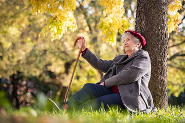Fototapeta Senior woman relaxing at park during autumn season obraz