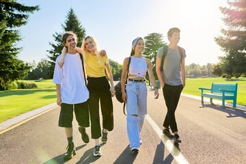Obraz Outdoor, four teenagers walking together on road - fototapety do salonu