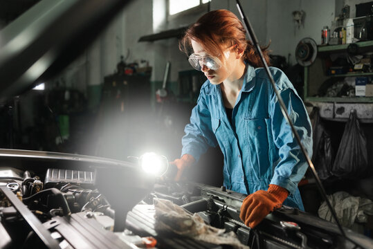 auto locksmith girl inspects the engine of the car illuminating the light of the lamp. Garage or auto repair shop and a woman at work in overalls and glasses. Machine repair concept.