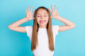 Obraz Photo of sweet brown hair little girl hands head tongue out wear white t-shirt isolated on blue color background - fototapety do salonu