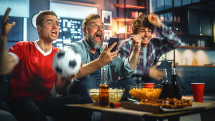 Fototapeta Night at Home: Three Soccer Fans Sitting on a Couch Watch Game on TV, Use Smartphone App to Online Bet, Celebrate Victory when Sports Team Wins. Friends Cheer Eat Snacks, Watch Football Play. obraz