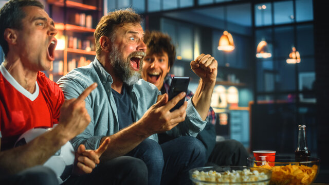 Night at Home: Three Soccer Fans Sitting on a Couch Watch Game on TV, Use Smartphone App to Online Bet, Celebrate Victory when Sports Team Wins. Friends Cheer Eat Snacks, Watch Football Play.