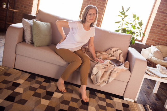 Portrait of elderly retired grey-haired woman sitting on sofa suffering feeling back pain at home house indoors modern brick loft interior