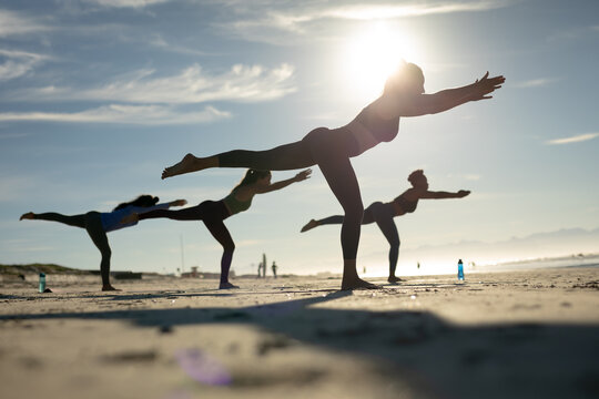 Group of diverse female friends practicing yoga at the beach