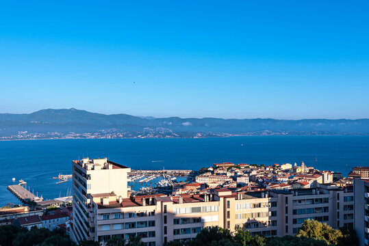 Aerial view of the corsican Ajaccio city with modern buildings on the foreground and the Mediterranean sea and mountains on the background. France 2021