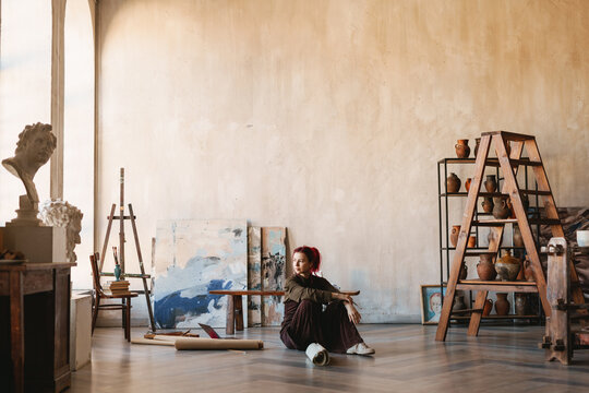 Young woman artist sitting on a floor of an art studio