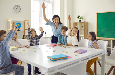 Fototapeta Happy clever enthusiastic school children and teacher raising hands. Confident preschoolers or first grade students sitting around big classroom table, learning letters, reading books and having fun obraz