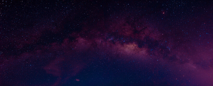 Milky way in the night sky and stars on dark background with noise and grain. Photo taken with long exposure and white balance selected.