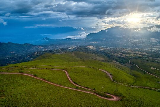 Aerial view of the winding sandy road from the Sanetti plateau to the green, tree-covered landscape of the Herenna forest. Sunset over Bale mountains, Ethiopia. Traveling around Ethiopia.