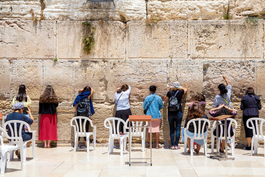 women near Wailing Wall or Western Wall, in Islam as Buraq Wall was built from ancient limestone. It is relatively small segment of far longer ancient retaining