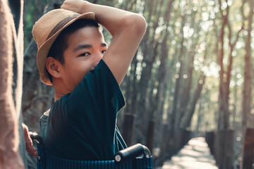 Fototapeta Confident of Asian disabled teen boy on wheelchair smiling face with his parent on the wood bridge and nature forest background, Lifestyle in the education age of happy special need child concept. obraz