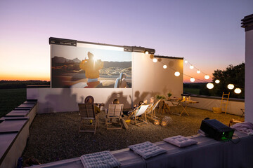 Fototapeta Small group of people watching movie on the rooftop terrace at sunset. Open air cinema concept. Romantic leisure and entertainment on the roof of a country house obraz