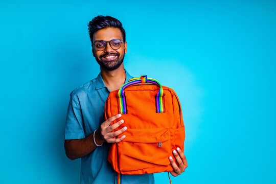 handsome young bearbed indian man with eye glasses in blue cotton t-shirt with orange rainbow backpack in studio background