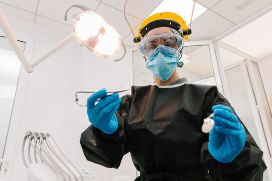 Dentist with Face Shield Working